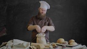 Kocken kontrollerar kvaliteten av mjölet korsade därefter hans händer och leblickar på kameran stock video
