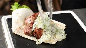 Kocken lägger grillat kött på en platta