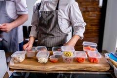 Kocken lägger ut krusen med mellanrum av produkter för att laga mat Mästarklass i köket Processen av matlagning Begrepp med mänsk arkivbild