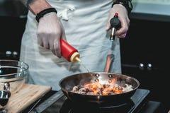 Kocken lagar mat den lilla bläckfisken på en metallstekpanna arkivfoto