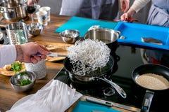 Kocken lagar mat funchozu i olja Mästarklass i köket Processen av matlagning Begrepp med mänskliga fotspår tutorial Närbild arkivbilder