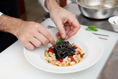 Kocken lagar mat pasta på kommersiellt kök Royaltyfria Bilder