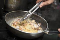 Kocken lagar mat spagettiallavongole Arkivbild