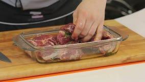 Kocken marinerar snidit kött för biff stock video