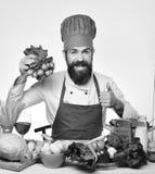 Kocken med den lyckliga framsidan i likformig sitter vid tabellen med grönsaker och kitchenware Mannen med skägget rymmer på rädi Royaltyfria Bilder