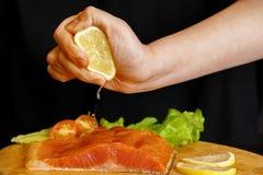 Kocken pressar citronjuice på röd fisk arkivfoto