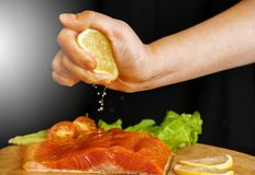Kocken pressar citronjuice på röd fisk royaltyfri bild