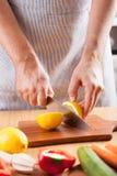 Kocken räcker den bitande citronen i kök Royaltyfri Fotografi