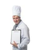Kocken rymmer en meny i handen för kunden Arkivfoton