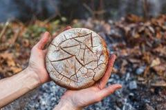 Kocken rymmer i hans händer brödet som bakas på kolen av branden royaltyfria foton