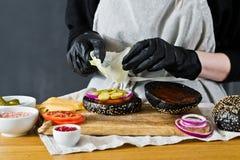 Kocken sätter grönsallat på en ostburgare Begreppet av att laga mat en svart hamburgare Hemlagat hamburgarerecept fotografering för bildbyråer