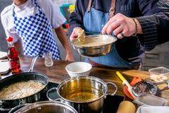 Kocken sätter skivorna av fisken med smet i pannan med smör Mästarklass i köket Processen av matlagning Begrepp med mänskliga fot royaltyfri fotografi