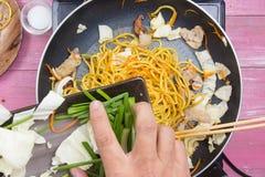 Kocken satte att skiva av vårlöken för att laga mat Arkivfoton