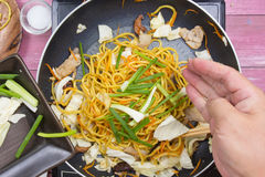 Kocken satte att skiva av vårlöken för att laga mat Royaltyfri Bild