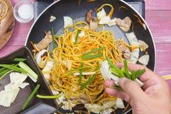 Kocken satte att skiva av vårlöken för att laga mat Fotografering för Bildbyråer