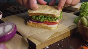 Kocken slutför smörgåsen med skinka, och sallad på träbrädet i strålen av ljus, kockens hand slutför lager videofilmer
