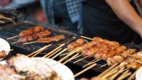 Kocken som använder en laga mat borste, sätter sås på höna- och grisköttkebaber, ultrarapid Smaskig köttmat i gatamarknaden arkivfilmer