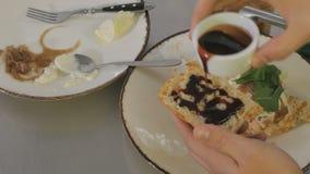 Kocken som bevattnar sås stycket av bröd och som sätter det på en smörgås lager videofilmer