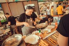 Kocken som förbereder asiatisk mat med kryddor, och grönsaker i ett enormt wokar Royaltyfri Fotografi