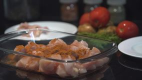 Kocken som tillfogar kryddor med en sked på överkanten av det rå fega bröstet, kock lagar mat fega bröst stock video
