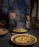 Kocken steker pannkakor i en gjutjärnpanna Ethno-stil royaltyfri fotografi