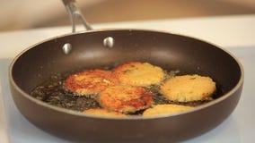 Kocken steker veggiehamburgare på en panna arkivfilmer