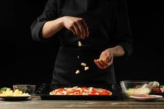 Kocken strilar pizza med ananasskivor Frysning i rörelse Ett begrepp av läcker mat och sund mat På en svart royaltyfri foto