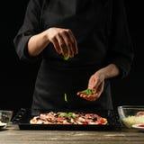 Kocken strilar pizza med basilikasidor Frysning i rörelse Ett begrepp av läcker mat och sund mat På en svart bakgrund arkivbilder