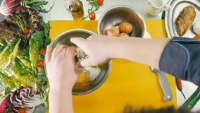 Kocken tillfogar mjölka och pepprar till rå ägg stock video
