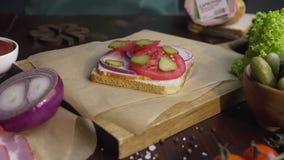 Kocken tillfogar skivade knipor till smörgåsen med skinka och grönsaker på träbrädet i strålen av ljus som gör av arkivfilmer