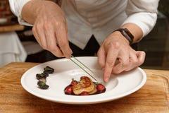 Kocken tjänar som foiegras royaltyfria foton