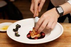 Kocken tjänar som foiegras royaltyfri fotografi