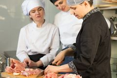 Kocken undervisar deltagaren i utbildning per grupp m?nniskor att klippa en h?na M?starklass p? bakgrunden av k?ket arkivfoto