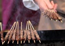 Kockens hand vänder köttsteknålarna av grillat nötkött Royaltyfri Bild