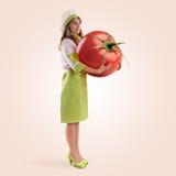 Kockflicka som rymmer en stor tomat royaltyfri bild