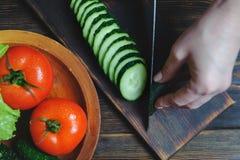 Kockhänder klippte en gurka med en kniv på en skärbräda royaltyfri bild