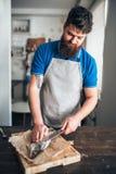 Kockhänder med den kniv klippta upp fisken på skärbräda Arkivfoto