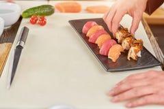 Kockhänder som förlägger nigirisushi på plattan Arkivfoton