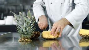 Kockhänder som skivar ananas i ultrarapid Kockhänder som hugger av ny frukt arkivfilmer