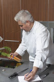 KockHolding Carrots And handstil i anteckningsbok royaltyfria foton