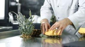 Kockklippananas på kök Closeupkockhänder som hugger av sund frukt arkivfilmer