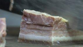 Kockkocken klipper det stora stycket av rimmat griskött på träskärbräda med kniven, arkivfoto