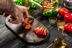 Kockmanmatlagning i köket Handen för man` s klipper moroten på ett träbräde royaltyfri bild