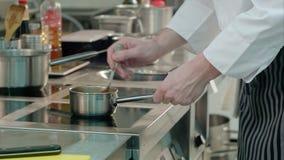 Kockmannen räcker att kontrollera mål som lagas mat på ugnen arkivfilmer