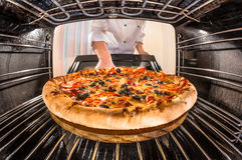 Kockmatlagningpizza i ugnen arkivfoton