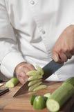 KockSlicing Cucumber On skärbräda royaltyfri fotografi