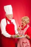 Kocken undervisar italiensk matlagning till hemmafrun Arkivbilder