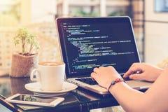 Koder för en programmeraremaskinskrivningkälla i en coffee shop Studera som arbetar, teknologi, frilans- arbete, affärsidéer för  royaltyfria bilder