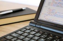 Kodifiera en website på den moderna anteckningsboken på kontoret Royaltyfri Bild