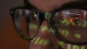 Kodreflexion i en hackerexponeringsglas En hacker som kodifierar i mörkt rum lager videofilmer